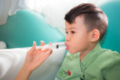 Asian kid take medicine from syringe by his mother's hand. Mother hand enter the medicine to her son by syringe Royalty Free Stock Photo