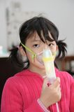 Asian kid taking respiratory Stock Photography