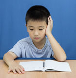 Asian kid thinking something to write Stock Image