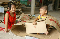 Asian kid, Vietnamese children. VINH LONG, VIET NAM- JULY 1: Unidentified Asian kid playing with carton, Vietnamese children with lovely face sit in store and Stock Photography