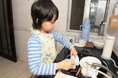 Asian kid washing dishes Royalty Free Stock Images