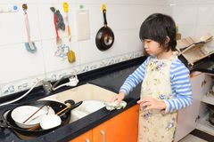 Asian kid washing dishes Royalty Free Stock Photos