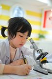 Asian kid writing report. Little Asian kid writing report after looking into microscope Stock Photos