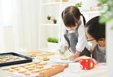 Asian Kid and young mother decorating cookie. Asian Kid and young mother decorating cookies in the kitchen stock images