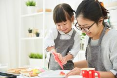 Asian Kid and young mother decorating cookies. Happy Asian Kid and young mother decorating cookies in the kitchen stock images