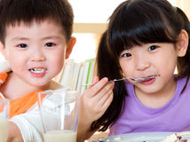 Asian kids eating. Little asian kids eating cake Royalty Free Stock Photo
