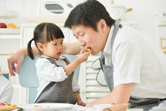 Asian Kids feeding cookie to her father. stock photo