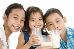 Asian kids with milk. Three asian kids with glasses of milk, isolated on white background royalty free stock images
