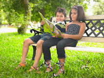 Asian kids in the park. Reading a book Stock Image