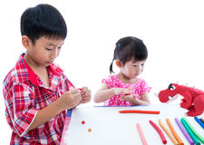 Asian kids playing with play clay on table. Strengthen the imagi Royalty Free Stock Image