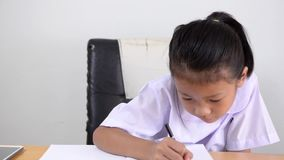 Asian kids - Thai girl in student uniform writing notebook stock video footage