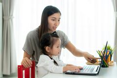 Asian kindergarten school girl  with mother video conference e-learning with teacher on laptop in living room at home.
