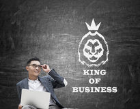 Asian king of business against blackboard. Portrait of Asian king of business with laptop and glasses sitting against blackboard with lion sketch on it. Mock up Royalty Free Stock Photography