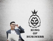 Asian king of business against concrete wall. Portrait of Asian king of business with laptop and glasses sitting against concrete wall with lion sketch on it Stock Images