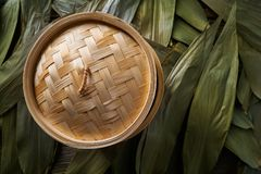 Asian kitchen bamboo steamer for steam cooking. Recipes on leafs Royalty Free Stock Photo