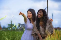 Asian Korean girl and black African American woman exploring together exotic tropical village on fresh rice field enjoying. Asian Korean girl and black African stock photos