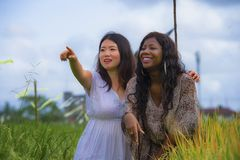 Asian Korean girl and black African American woman exploring together exotic tropical village on fresh rice field enjoying. Asian Korean girl and black African stock image