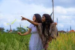 Asian Korean girl and black African American woman exploring together exotic tropical village on fresh rice field enjoying. Asian Korean girl and black African royalty free stock photos