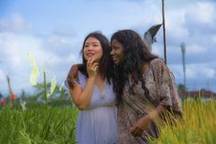 Asian Korean girl and black African American woman exploring together exotic tropical village on fresh rice field enjoying. Asian Korean girl and black African royalty free stock images
