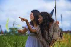 Asian Korean girl and black African American woman exploring together exotic tropical village on fresh rice field enjoying. Asian Korean girl and black African stock photo