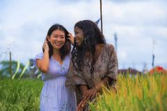 Asian Korean girl and black African American woman exploring together exotic tropical village on fresh rice field enjoying. Asian Korean girl and black African royalty free stock photo