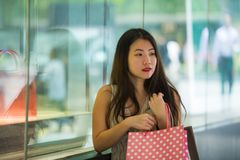Asian Korean happy woman carrying shopping bags walking on street next to clothing window store after buying beauty stuff in femal royalty free stock images