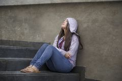 Asian Korean student woman or bullied teenager girl sitting outdoors on street staircase victim of bullying feeling scared and. Young sad and depressed Asian royalty free stock photo