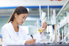 Asian Laboratory scientist working at lab with test tubes. One Female Chinese Laboratory scientist working at lab with test tubes Stock Photo