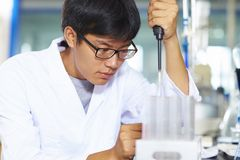 Asian Laboratory scientist working at lab with test tubes. One male Chinese Laboratory scientist working at lab with test tubes Stock Photo