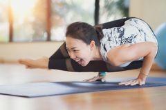 Asian lady atke Yoga exercise in fitness center. With sunset light at windows Stock Images