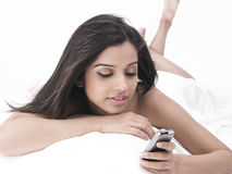 Asian lady in bed with cell phone Royalty Free Stock Image