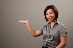 Asian lady in business attire. Presenting something to the left Royalty Free Stock Photography