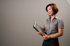 Asian lady in business attire, holding a notebook. Computer Stock Image