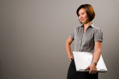 Asian lady in business attire, holding a notebook. Computer Royalty Free Stock Photography