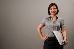 Asian lady in business attire, holding a notebook. Computer Royalty Free Stock Photos