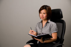 Asian lady in business attire, holding pen. And organizer, deep in thought Royalty Free Stock Photos