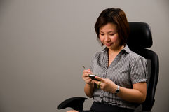 Asian lady in business attire, using a PDA. (portable digital assistant Royalty Free Stock Images