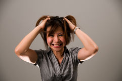 Asian lady in business attire, very frustrated. Asian lady in business attire, feeling very frustrated, tearing her hair out Royalty Free Stock Photos