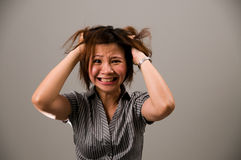 Asian lady in business attire, very frustrated. Asian lady in business attire, feeling very frustrated, tearing her hair out Stock Image