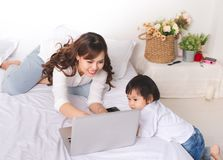Asian lady in classic suit working on laptop at home with her ba. By girl royalty free stock photos
