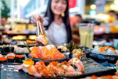 Asian lady eat a Salmon fish sashimi and Sushi in Japanese restaurant stock photo