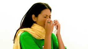 Asian lady in green tshirt and yellow scarf sneezing stock footage