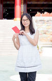 Asian lady holding red envelope or Ang-pow . Royalty Free Stock Image