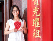 Asian lady holding red envelope or Ang-pow . Royalty Free Stock Photography