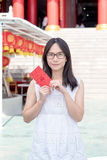 Asian lady holding red envelope or Ang-pow . Royalty Free Stock Photos