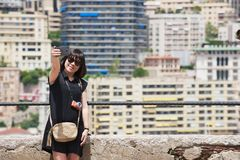 Asian lady makes selfie with a smartphone at the viewpoint in Monaco. Stock Image