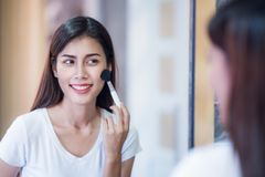 Asian lady makeup bewore go out to working with mirror in bed room stock photography