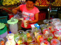 Asian lady making fruit milkshakes lassi. Banana apples pineapple fruit milkshakes lassi's being made with lots of colours stock images