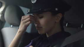 Asian lady police officer rubbing nasal bridge and taking off hat after hard day stock video footage