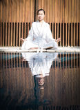 Asian Lady practicing Yoga. On the wooden desk royalty free stock photo